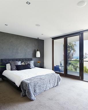Κρεβατοκάμαρα σε εξοχική κατοικία με συρόμενα κουφώματα. Η μπαλκονόπορτα είναι κατασκευασμένη από κουφώματα αλουμινίου.